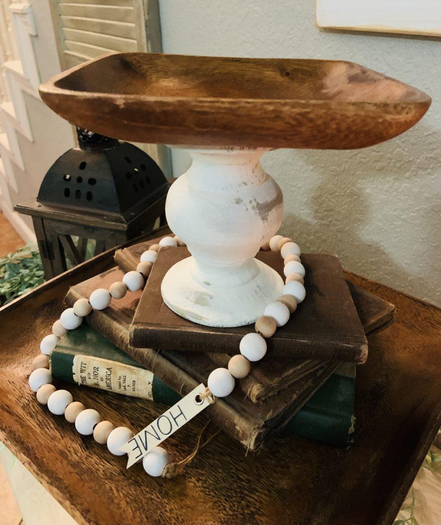 farmhouse pedestal tray sitting on stack of books